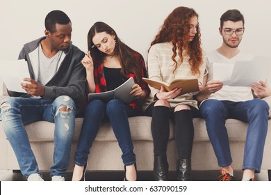 Diverse students preparing for exam, sitting on sofa in living room and studying, studio shot