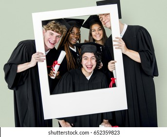 Diverse Students wearing Cap and Gown Holding Photo Frame Studio Portrait