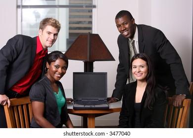 diverse team around computer looking