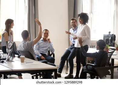 Diverse team in coworking space voting some colleagues agree raises hands. Positive black leader woman with creative group of businesspeople discussing sharing ideas together in office at meeting