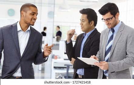 Diverse team of interracial businesspeople having discussion at international corporate office.