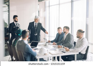 Diverse team of middle-aged multiethnic male investors, leading by senior aged experienced Director, cooperating on developing common investments project