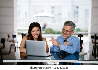 A diverse team of an older Caucasian man and a Chinese Asian woman have business meeting outdoors. They are having a discussion over a laptop computer and are professionally dressed.