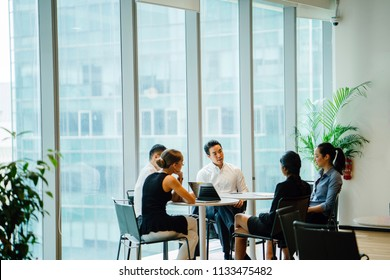 A diverse team sit around a table in a meeting room to have a business meeting to discuss plans. The group is international with Asian and White team members and they are all professionally dressed.