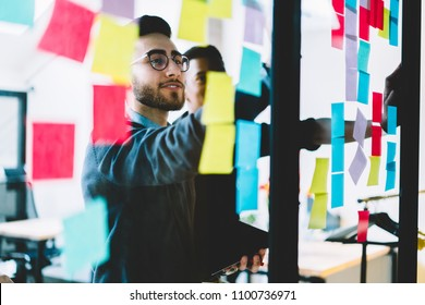 Diverse team of skilled young people learning foreign words from colorful stickers glued on glass wall during collaborative process in office interior.Multicultural students using paper sticky notes
