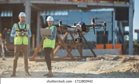 Diverse Team of Specialists Pilot Drone on Construction Site. Architectural Engineer and Safety Engineering Inspector Fly Drone on Commercial Building Construction Site Controlling Design and Quality
