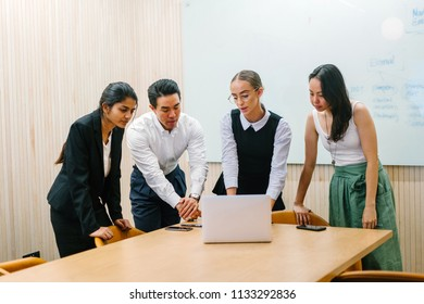 A diverse team stand around a laptop for a business discussion in a meeting room in the office. They are ethnically diverse and includes a Caucasian, Indian and Eurasian woman and a Chinese man.