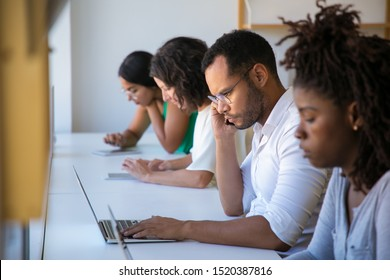 Diverse team working on project in office. Man and women sitting at long desk, using laptops and tablets, looking at screen, talking on cell. Digital gadgets for business concept