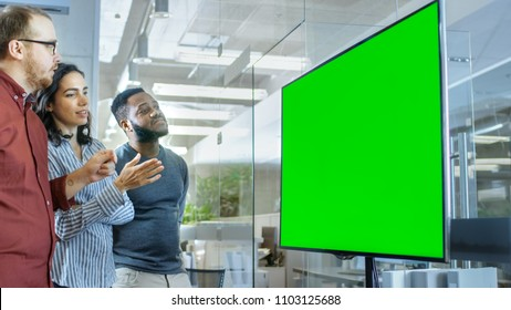 Diverse Team of Young People in Conference Room Have Discussion about Green Screen Chroma Key Template Shown on a Presentation TV.