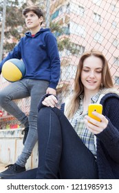 Diverse teenager studends relaxing together in college sports ground using smartphone and holding basketball, outdoors. Trendy adolescents technology, leisure recreation lifestyle.