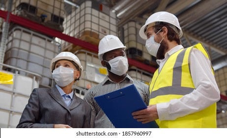 Diverse warehouse inspectors wearing safety mask discussing distribution plan on clipboard. Industrial warehouse engineer, manager and owner in protective mask inspecting distribution center