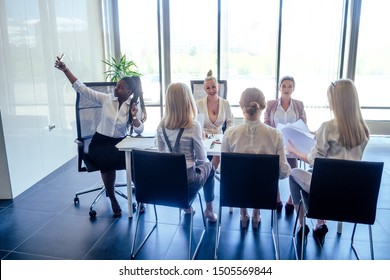 Diverse women applaud at modern centre business meeting.