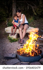 Diverse women and a cute boy roasting a marshmallow together over an open campfire while on an outdoor camping trip in the mountains