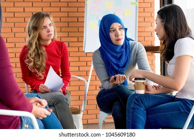 Diverse women sharing problems and support eacher in group meeting therapy