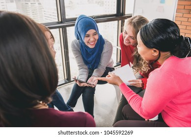 Diverse women sitting in circle enjoying sharing stories in group meeting