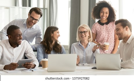 Diverse workers have fun watch video joke online use pc drink coffee break sitting in office room workplace, different ages ethnicity employees members laughing at training with mature business coach