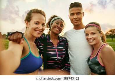 Diverse yoga class of cheerful millennial friends takes a selfie at sunset in nature park