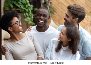 Diverse young cheerful people black and caucasian girls and guys embracing and joking, friends spending time together having fun in summer cafe. Multinational friendship, good warm relations concept