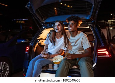 Diverse young couple having romantic date. Cheerful guy and his girlfriend watching a movie, sitting together in car trunk in front of screen in open air cinema. Entertainment ideas. Horizontal shot