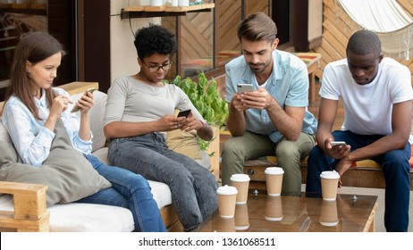 Diverse young friends sitting together with technology holding mobile in hands using social media play games in cafe, group of multi-ethnic people using phones messaging, teen mobile addiction concept