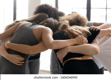 Diverse young people embracing, standing in circle, promising help, support and unity, fitness center staff engaged in team building activity, motivated for teamwork success, achievement