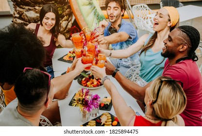 Diverse young people having fun celebrating cocktails - Happy friends enjoying time at home party sitting in villa backyard - Summer lifestyle and food and drink concept.