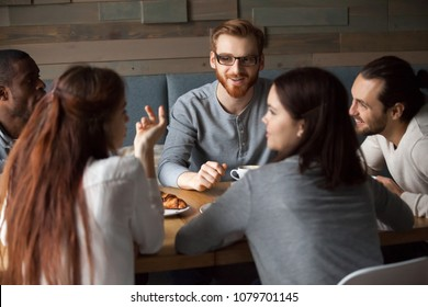 Diverse young people talking and having fun together in cafe, girls chatting sharing coffeehouse table with multiracial friends, multi-ethnic millennials enjoying pleasant discussion in public place