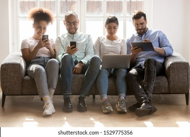 Diverse young people using electronic devices, phones, laptop, tablet, sitting in row on couch, obsessed by gadgets, chatting in social network, watching video, playing games, ignoring each other