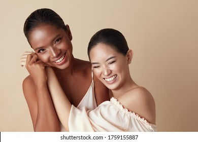 Diversity. Beauty Models Portrait. Cheerful Asian And Mixed Race Women Bonding Hands And Laughing. Different Ethnicity Female With Natural Makeup Standing Together Against Beige Background.