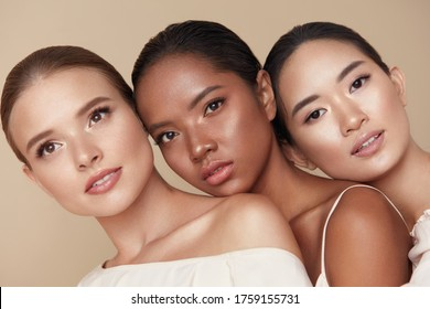 Diversity. Beauty Portrait Of Different Ethnicity Women. Multi-Ethnic Models Standing Together Against Beige Background. Three Tender Female Friends With Nude Makeup And Perfect Smooth Skin.