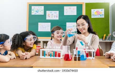 Diversity children doing a chemical experiment in laboratory at school. Portrait of happy kids at elementary school learning science chemistry with asian teacher. Fun study back to school concept.