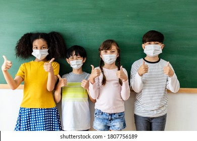 Diversity of children students wearing medical masks in the classroom. Students stand in a row in front of the blackboard with thumbs up.  Prevention of the coronavirus outbreak And new normal Concept