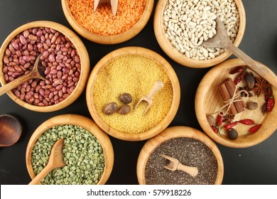 Diversity colored beans and lentil in wooden and pot spoon on black background