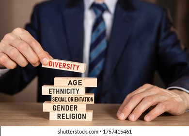 Diversity concept. Business man building stack from wooden blocks with text Diversity, Age, Ethnicity, Sexual Orientation, Gender, Religion.