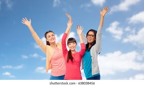 diversity, ethnicity and people concept - international group of happy smiling different women having fun over blue sky and clouds background