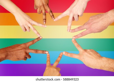 diversity, gay pride, tolerance, international and people concept - group of hands showing peace hand sign over rainbow background