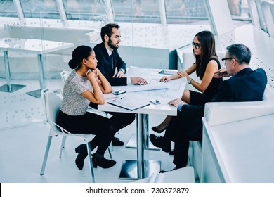 Diversity group of professional architects showing blueprints and sketches to client discussing details at meeting table, male and female engineers drafting together creating plans with confident boss