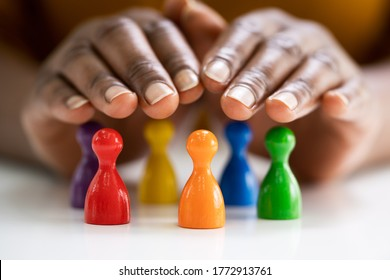 Diversity And Inclusion Concept. Hand Protecting Hand Colored Staff Pawns In Circle