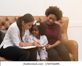 Diversity Lesbian sitting with cute African toddler girl in between. Happiness and family bonding in LGBTQ family, LGBT lifestyle.