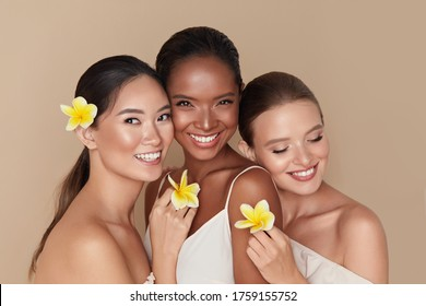 Diversity. Natural Beauty Portrait. Multi-Ethnic Women With Tropical Flowers Standing Together. Asian, Mixed Race And Caucasian Models With Nude Makeup And Healthy Skin Holding Plumeria.