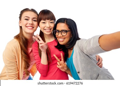 diversity, race, ethnicity and people concept - international group of happy smiling different women over white taking selfie and showing peace hand sign