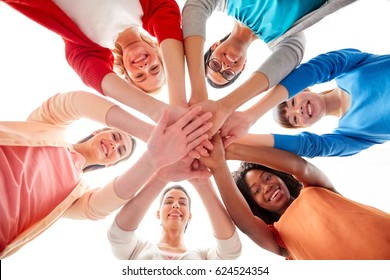 diversity, race, ethnicity and people concept - international group of happy smiling different women over white holding hands together