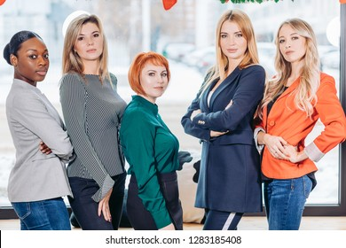 diversity, race, height, success and people concept - multiracial group of happy women of different rac, and height standing against window, looking at camera with confident and serious look.