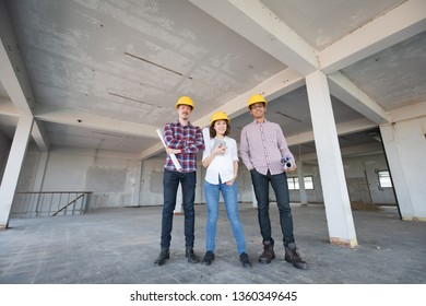 Diversity team of engineer, one woman and two men, standing together and smiling to camera while working in indoor building construction site.