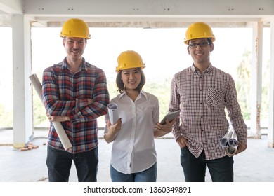 Diversity team of engineer, one woman and two men, standing together and smiling to camera while working in construction site.