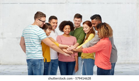 diversity, teamwork, cooperation, ethnicity and people concept - international group of happy smiling men and women holding hands together over wall background