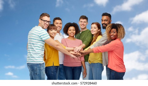 diversity, teamwork, race, ethnicity and people concept - international group of happy smiling men and women holding hands together over blue sky and clouds background