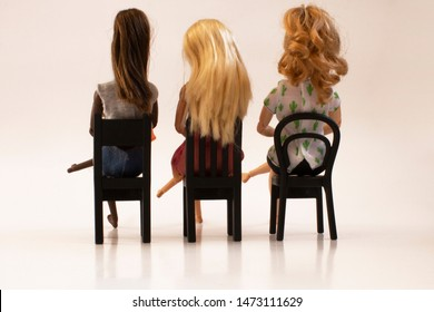 Diversity. Three dolls of different colors and hair sitting on black chairs, seen from the back. White background.