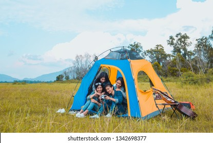 Diversity Young Asian women camping and resting at forest looking a photo in camera happy on weekend.