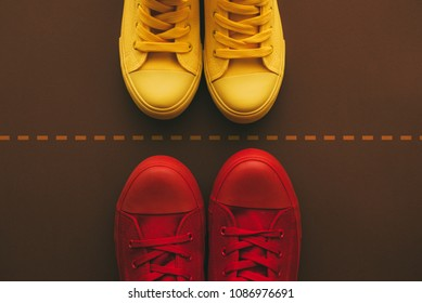 Divided couple separated by dashed line, breaking apart and divorcing concept with top view of two young people wearing sneakers
